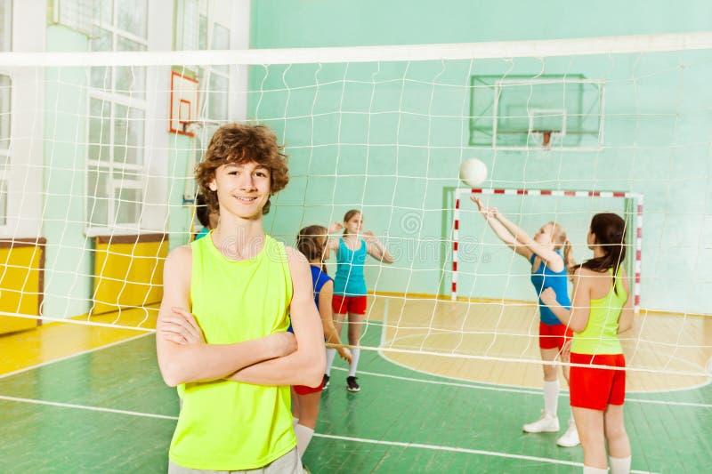 Ragazzo in abiti sportivi che stanno accanto alla rete di pallavolo fotografie stock libere da diritti