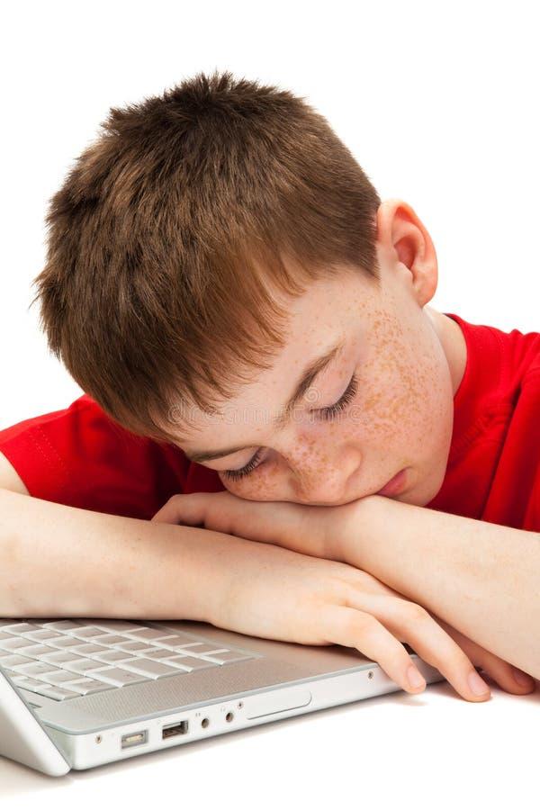 Ragazzo addormentato con un computer portatile fotografia stock libera da diritti