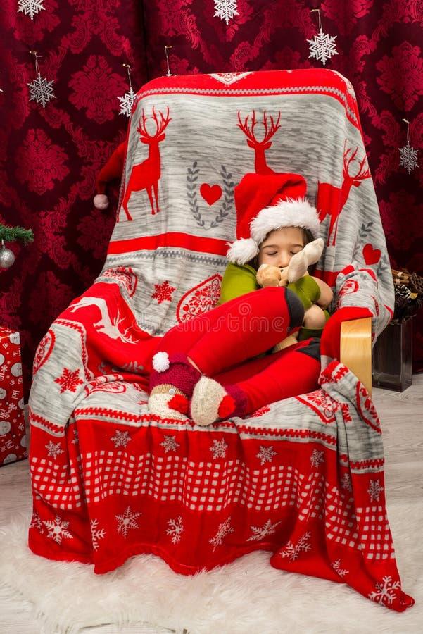 Ragazzo addormentato in peluche del giocattolo della renna della tenuta della sedia fotografie stock
