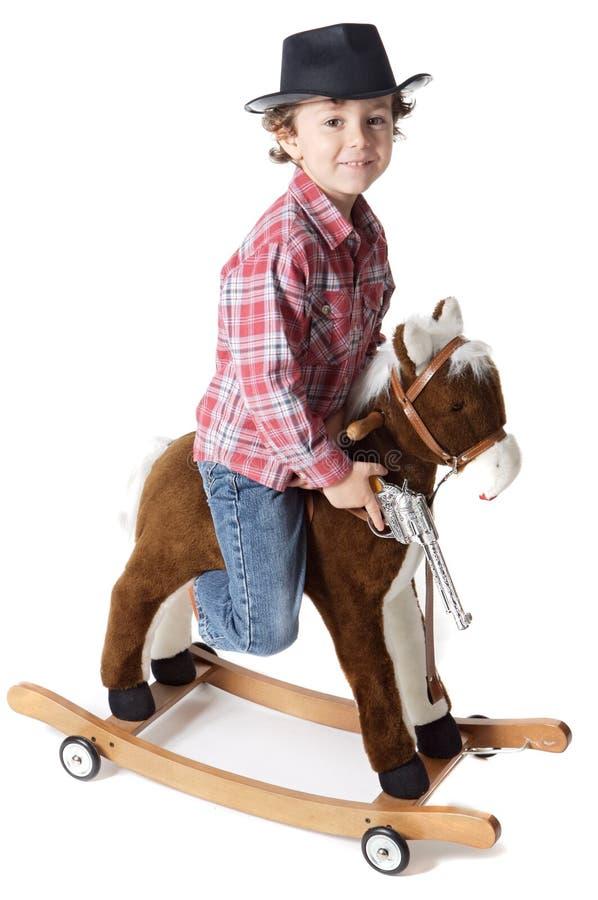 Ragazzo adorabile che gioca i cowboy con un cavallo di legno fotografia stock libera da diritti
