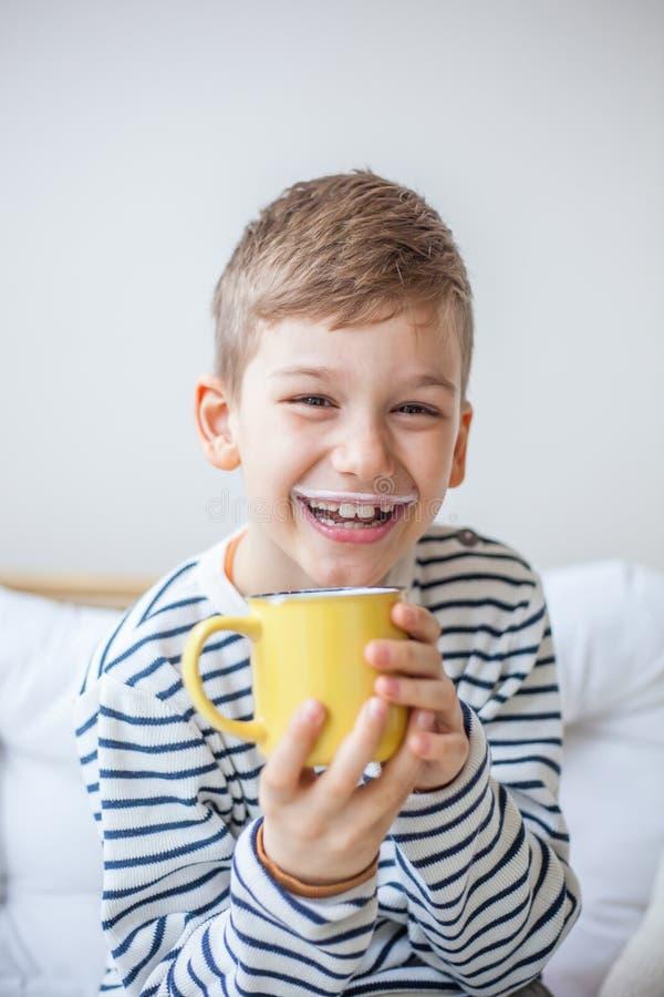 Ragazzo adorabile dei capelli biondi che sorride e che tiene una tazza gialla con latte fotografia stock