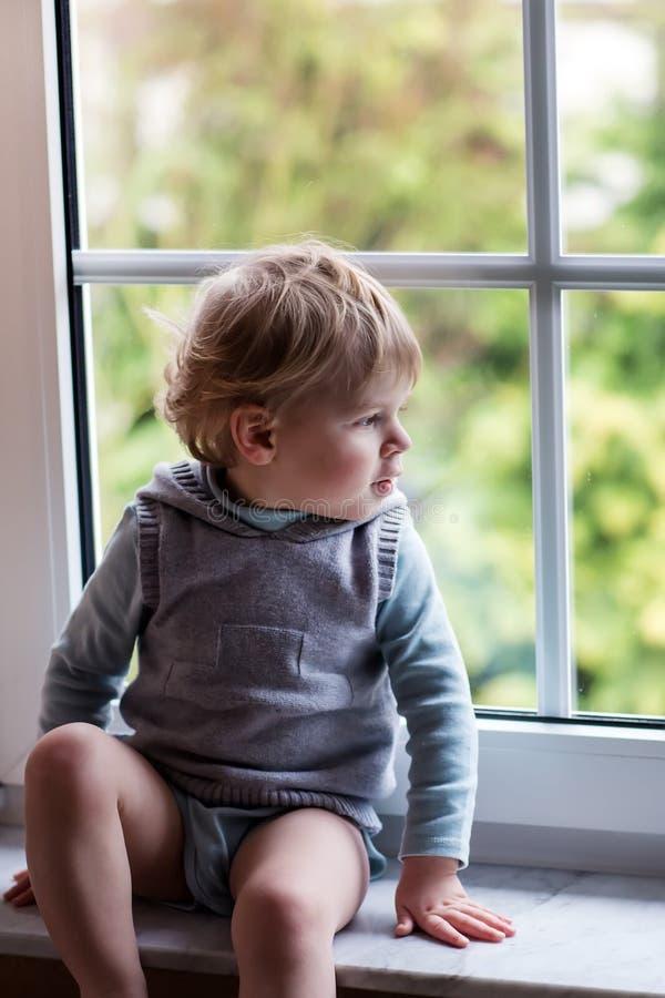 Ragazzo adorabile del bambino che guarda dalla finestra fotografia stock
