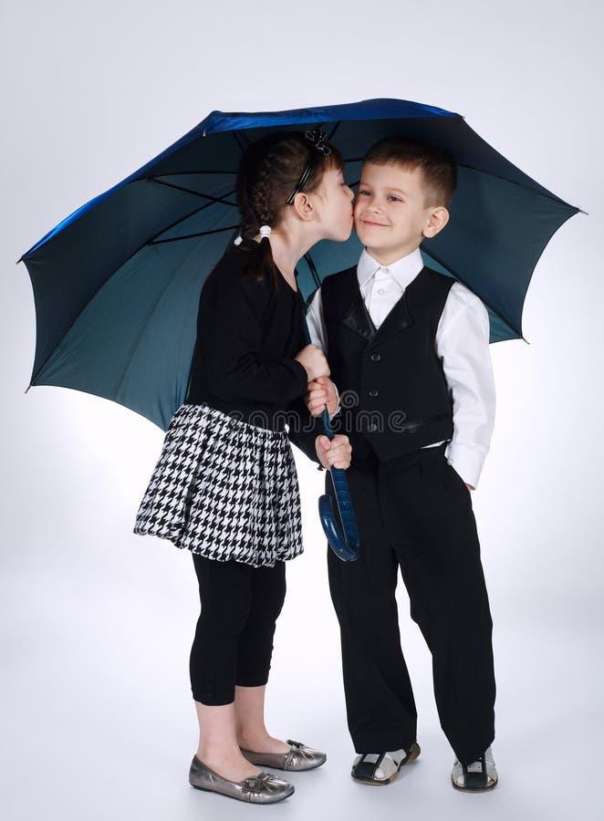 Ragazzo adorabile e ragazza che stanno sotto l'ombrello fotografia stock libera da diritti