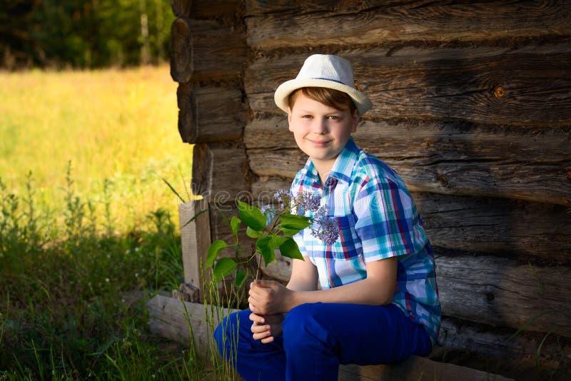 Ragazzo adorabile nell'odorare del cappello del lillà un mazzo dei fiori nella campagna fotografia stock libera da diritti