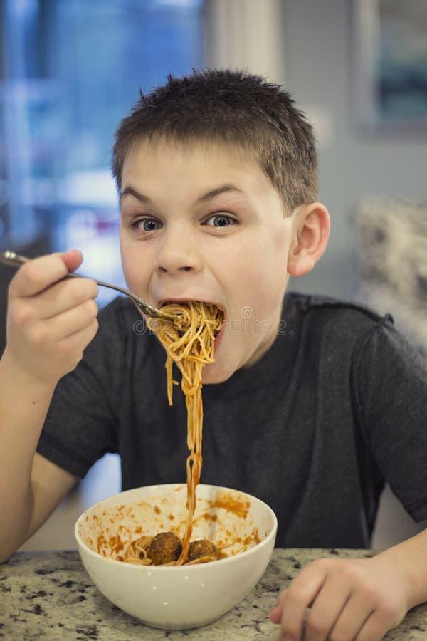 Ragazzo affamato ed emozionante che prende un morso enorme degli spaghetti fotografie stock