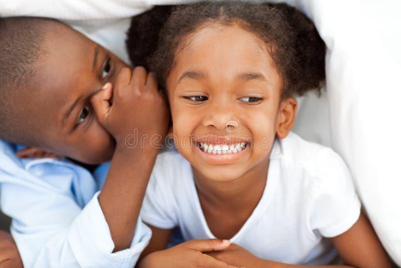 Ragazzo africano che bisbiglia qualcosa alla sua sorella immagini stock