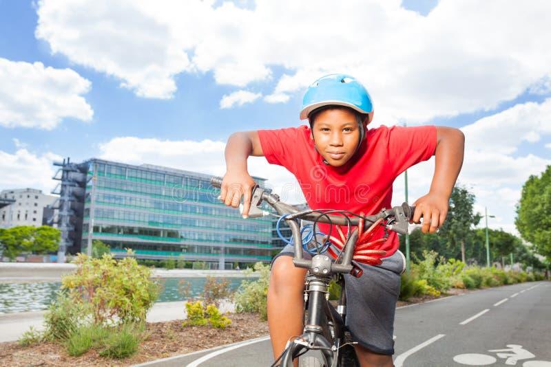 Ragazzo africano che guida la sua bici sulla pista ciclabile fotografie stock