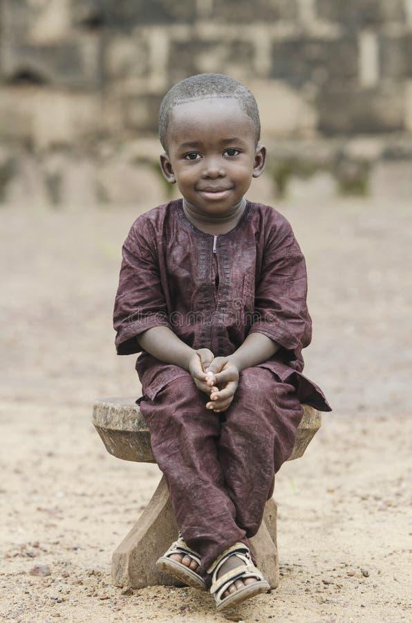 Ragazzo africano che si siede sul banco di legno e che esamina macchina fotografica con fondo vago immagine stock