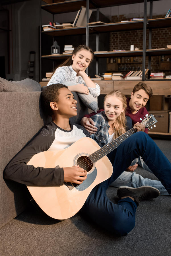 Ragazzo afroamericano che gioca chitarra acustic mentre i suoi amici che ascoltano a casa fotografia stock libera da diritti