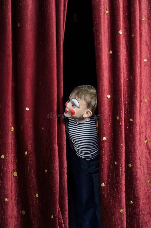 Ragazzo agghindato come tenda di Peeking Thru Stage del pagliaccio fotografie stock