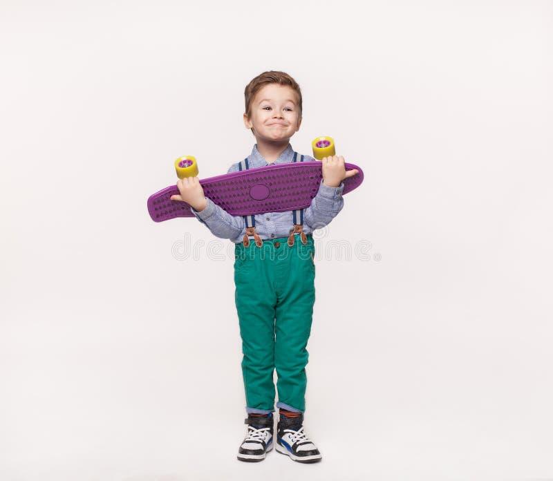 Ragazzo alla moda del bambino che tiene il suo pattino del regalo di compleanno fotografia stock libera da diritti
