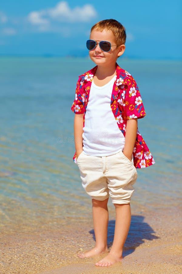 Ragazzo alla moda felice che sta in acqua sulla spiaggia tropicale fotografia stock