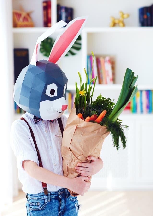 Ragazzo alla moda sveglio, nella maschera poligonale del coniglio di pasqua con una borsa in pieno dei verdi freschi della molla fotografia stock
