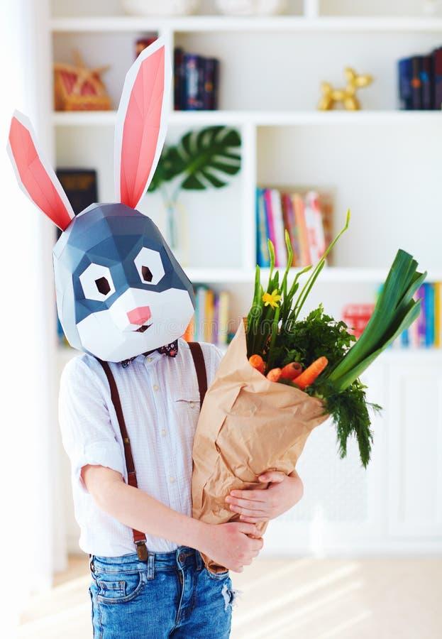Ragazzo alla moda sveglio, nella maschera poligonale del coniglio di pasqua con una borsa in pieno dei verdi freschi della molla fotografie stock