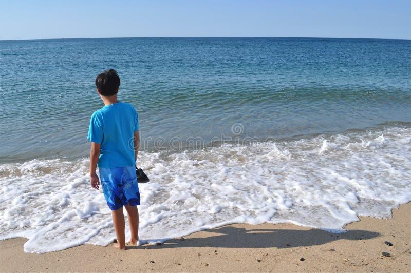 Ragazzo alla spiaggia blu fotografia stock libera da diritti