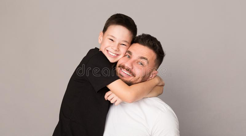 Ragazzo allegro che abbraccia con suo padre, ritratto felice della famiglia immagine stock libera da diritti