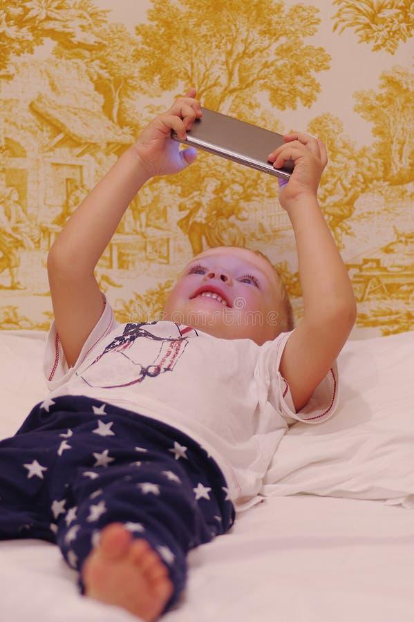 Ragazzo allegro che gioca nei giochi sul suo telefono cellulare che si trova sul letto fotografie stock