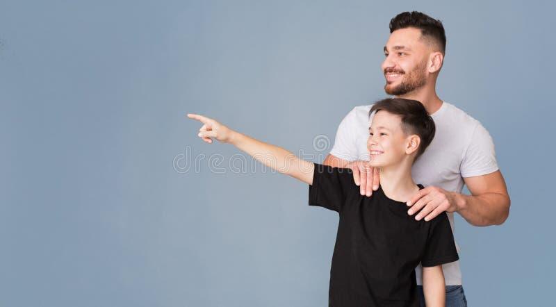 Ragazzo allegro che mostra qualcosa per il suo papà, indicando con il dito immagini stock libere da diritti