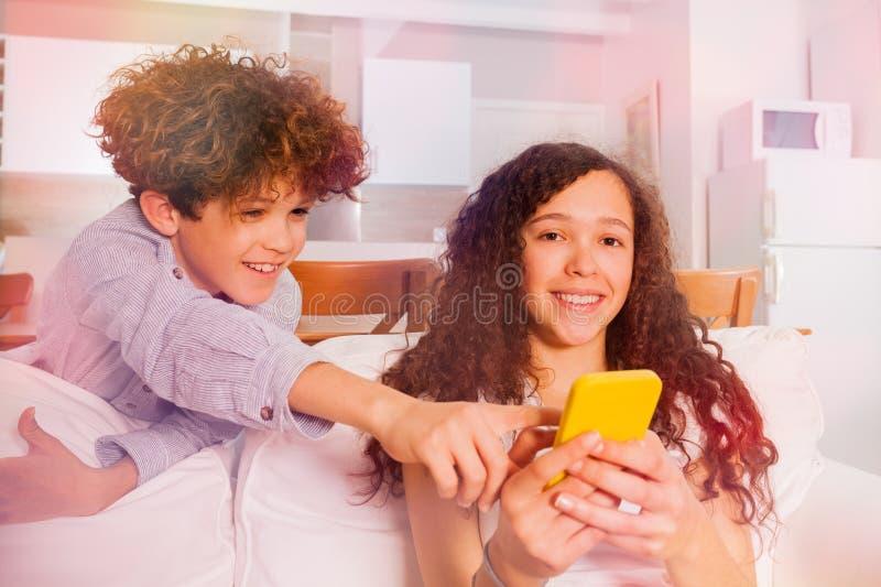 Ragazzo allegro e ragazza con il telefono cellulare sul sofà fotografia stock libera da diritti