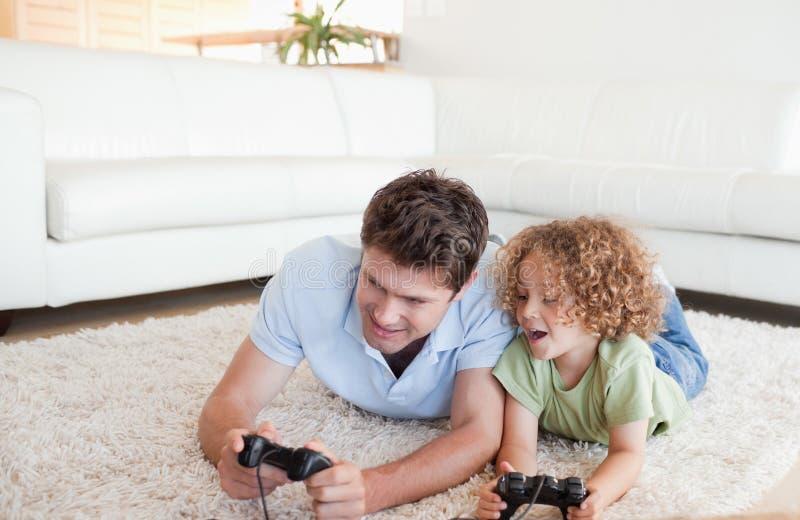 Ragazzo allegro e suo il padre che giocano i video giochi fotografia stock libera da diritti