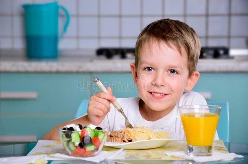 Ragazzo allegro sorridente che si siede alla tavola e ad esaminare di cena Th fotografia stock libera da diritti