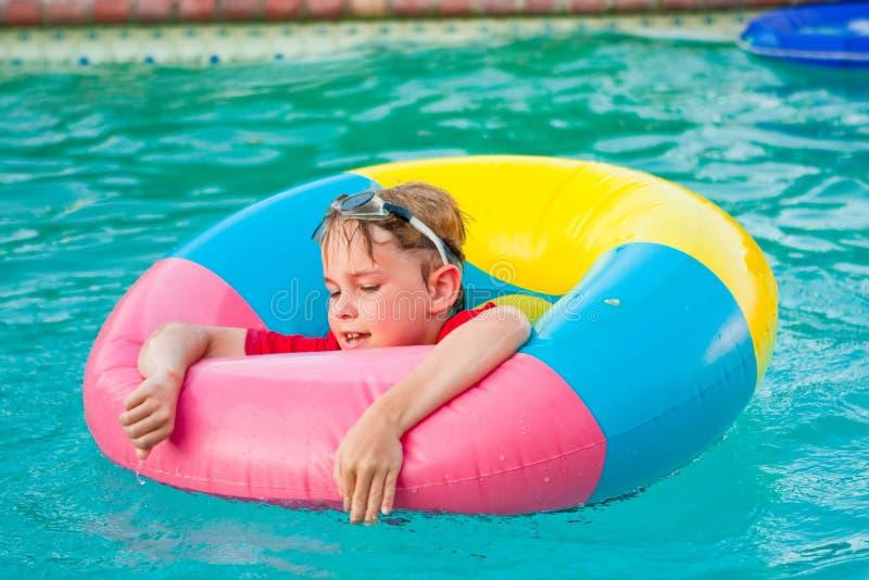Ragazzo in anello variopinto del galleggiante nella piscina fotografia stock libera da diritti