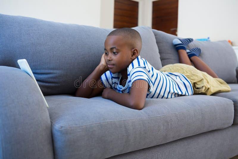 Ragazzo annoiato che esamina telefono cellulare mentre trovandosi sul sofà grigio immagine stock libera da diritti