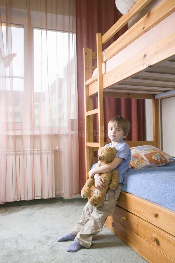 Ragazzo annoiato con il letto di Teddy Bear Leaning On Bunk fotografia stock libera da diritti