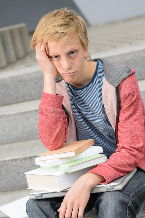 Ragazzo annoiato dello studente con i libri ed il computer portatile fotografia stock