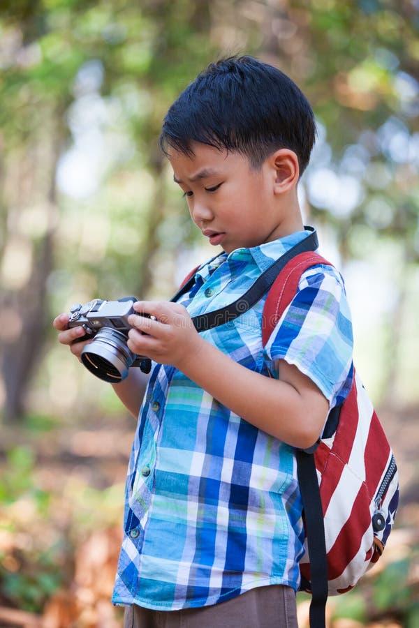 Ragazzo asiatico che controlla le foto in macchina fotografica digitale fotografia stock libera da diritti