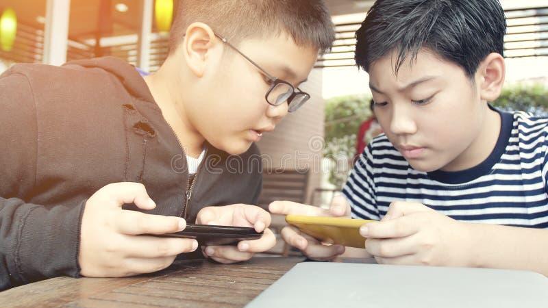 Ragazzo asiatico che gioca insieme gioco mobile sullo Smart Phone fotografia stock libera da diritti