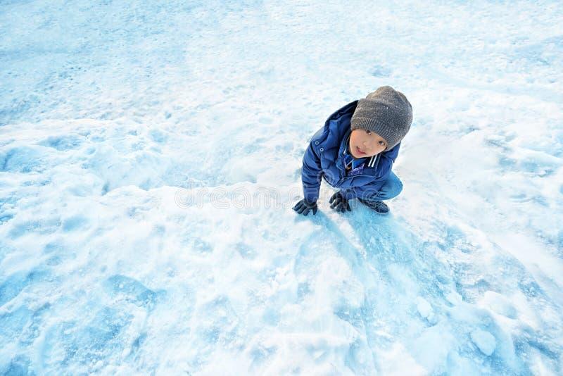 Ragazzo asiatico che gioca nella neve fotografie stock libere da diritti