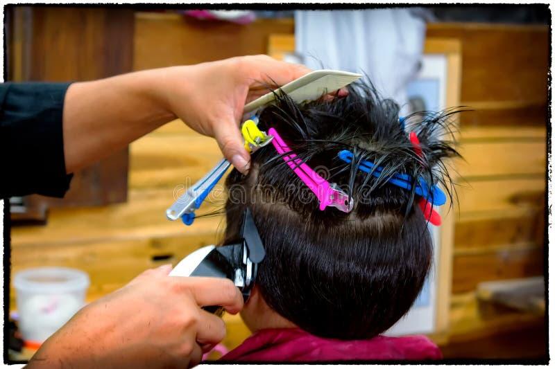 Ragazzo asiatico che riceve un taglio di capelli da uno stilista di capelli fotografia stock libera da diritti