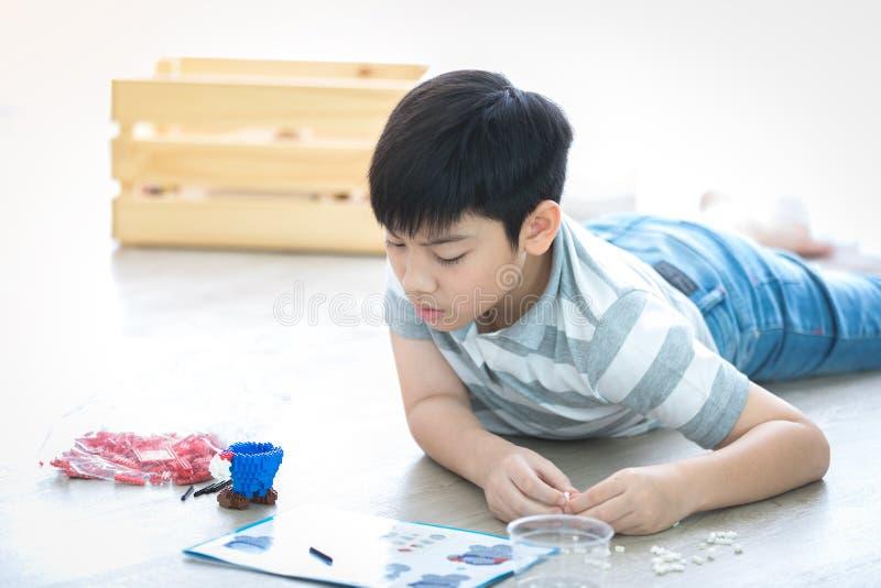Ragazzo asiatico che si trova e che gioca blocco di plastica a casa fotografie stock libere da diritti
