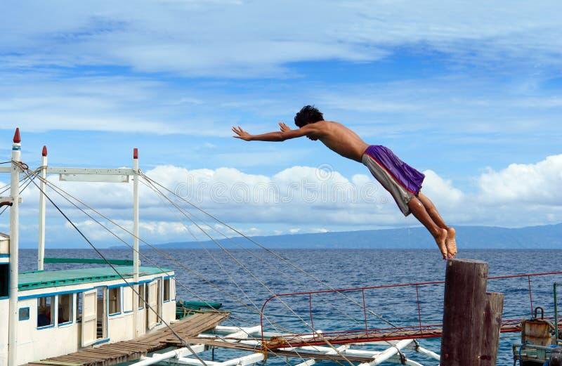 Ragazzo asiatico d'immersione in porta fotografie stock