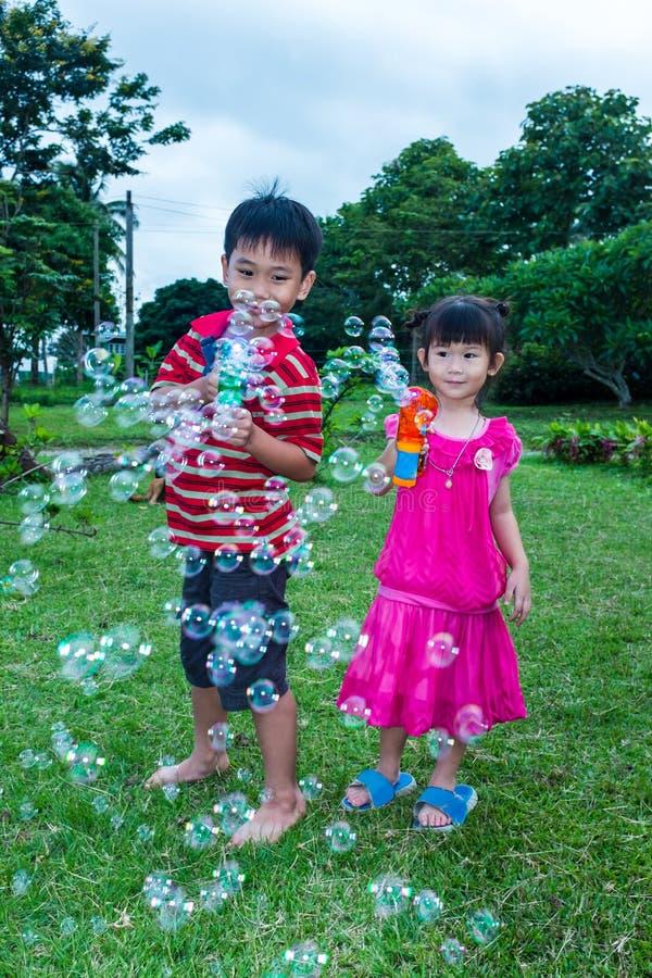 Ragazzo asiatico e ragazza adorabili che giocano sull'erba verde all'iarda Outdoo fotografia stock libera da diritti