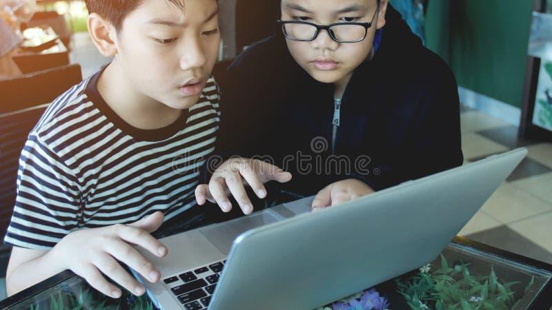 Ragazzo asiatico felice che scrive sul computer portatile fotografie stock libere da diritti