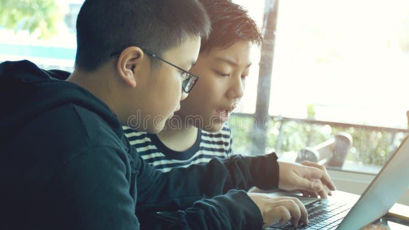 Ragazzo asiatico felice che scrive sul computer portatile fotografia stock libera da diritti