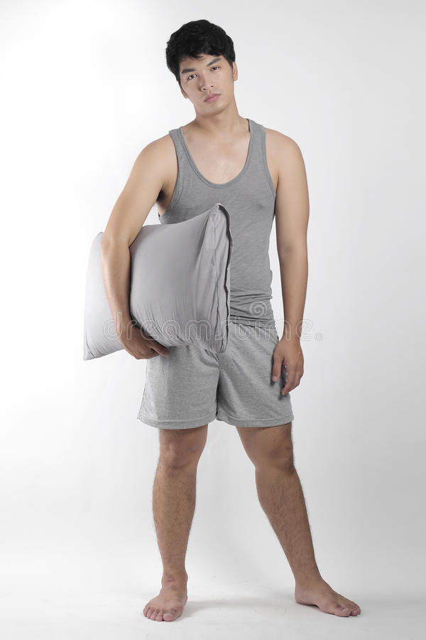 Ragazzo asiatico in pigiami grigi con un cuscino immagine stock libera da diritti