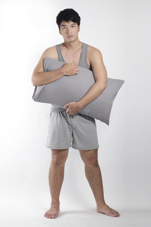 Ragazzo asiatico in pigiami grigi con un cuscino fotografia stock libera da diritti