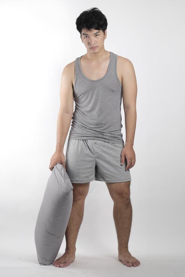 Ragazzo asiatico in pigiami grigi con un cuscino immagine stock