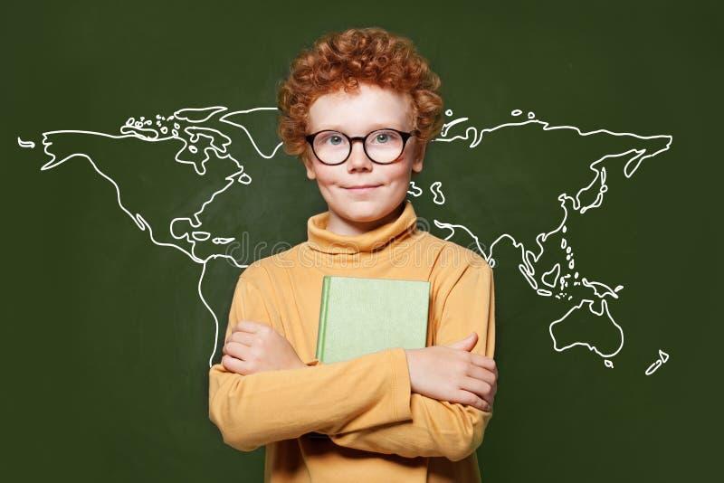 Ragazzo astuto del bambino con la mappa di terra sulla lavagna verde Concetto di protezione dell'ambiente fotografia stock libera da diritti