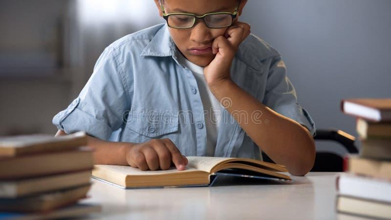 Ragazzo astuto in vetri che si siedono in libri di lettura delle biblioteche, letteratura educativa fotografia stock libera da diritti