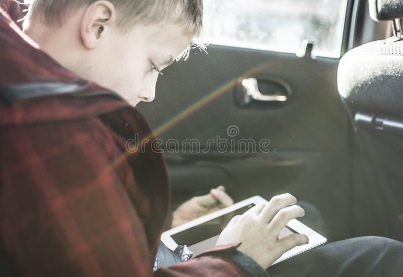 Ragazzo in automobile che gioca sul pc della compressa fotografia stock libera da diritti