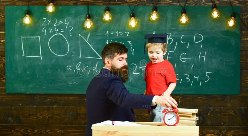 Ragazzo, bambino nel gioco laureato del cappuccio con il papà, divertendosi e rilassandosi durante la pausa della scuola Concetto immagini stock