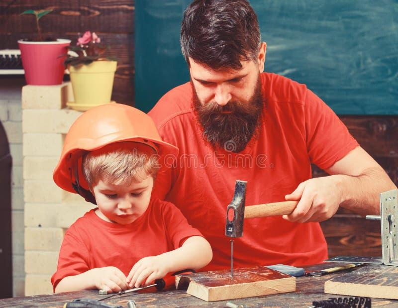 Ragazzo, bambino occupato in casco protettivo imparante a martellare le bullette per suole con il pap? Padre, genitore con la bar fotografie stock libere da diritti