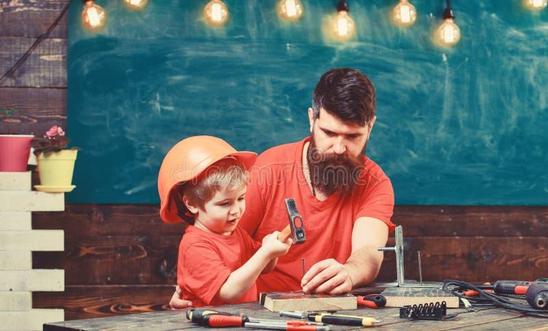Ragazzo, bambino occupato in casco protettivo imparante utilizzare martello con il papà Generi con la barba che insegna al piccol fotografia stock libera da diritti
