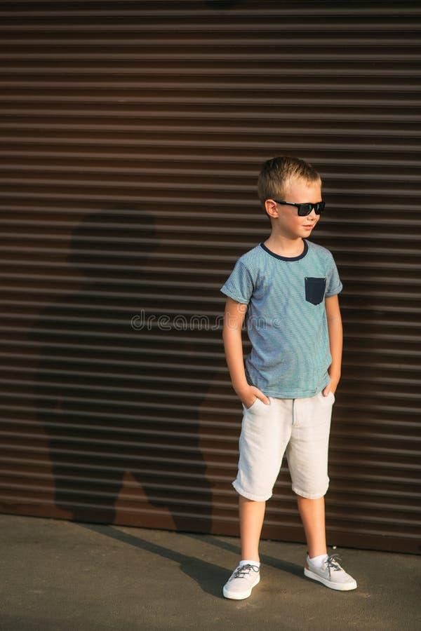 Ragazzo bello che sorride e che posa al fotografo Il bambino allegro cammina il parco Estate soleggiata del tempo immagini stock libere da diritti