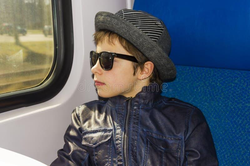 Ragazzo bello nei giri degli occhiali da sole sul treno fotografie stock libere da diritti