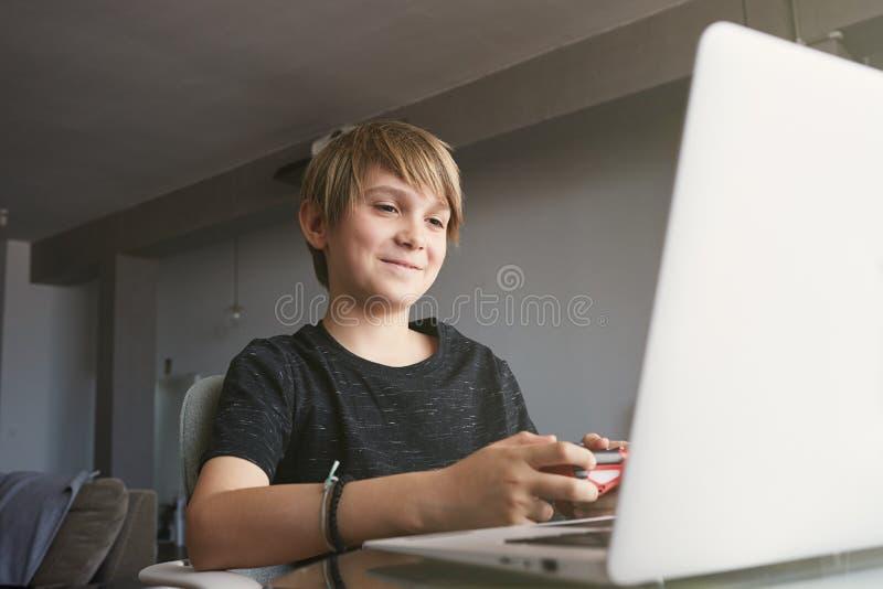 Ragazzo bello sorridente che utilizza computer portatile mentre sedendosi alla tavola nel salone a casa Esamini il taccuino fotografia stock